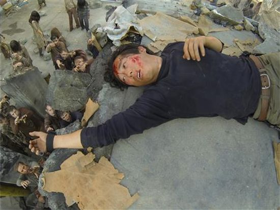 Glenn wakes up just out of reach of a horde.  Image Source: AMC