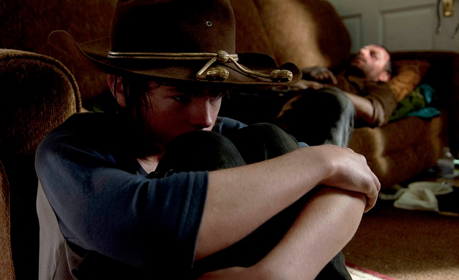 Carl waits for Rick to regain consciousness. Image Source: AMC